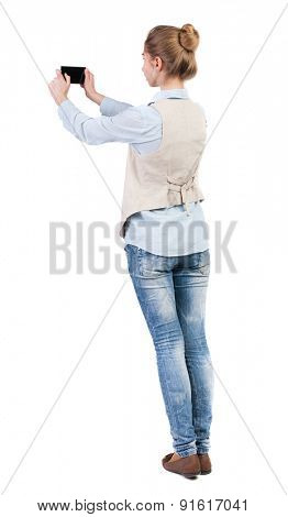 back view of standing young beautiful  woman  in vest and using a mobile phone. Rear view people collection.  backside view of person.  Isolated over white background. Girl doing selfie on your phone.
