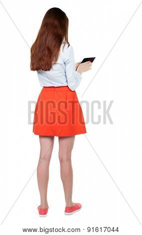 back view of standing young beautiful  girl with tablet computer in the hands of.   Isolated over white background.A woman in a red skirt standing and leafs through the information on the tablet.