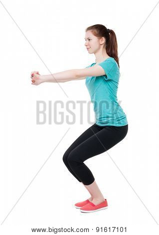 slim girl in sportswear is engaged in sports. She squats. Rear view people collection.  backside view of person.  Isolated over white background. Girl with a smile doing squats.