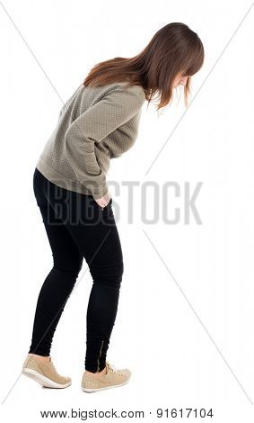 back view of standing young beautiful  woman in jeans looks down. girl  watching. Rear view people collection.    Isolated over white background. The girl looks at his feet with his hands in his pants