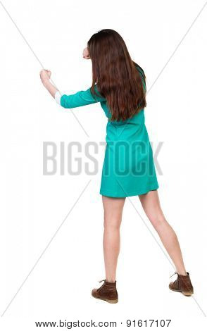 skinny woman funny fights waving his arms and legs. Isolated over white background. The girl in a dress beats foot in brown shoe. The girl in the green dress has a strict left hand.