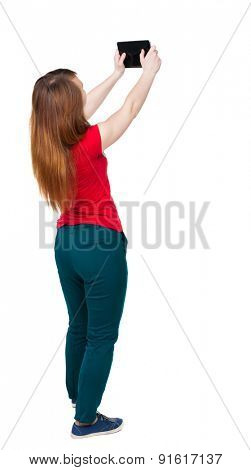 back view of standing young beautiful  girl with tablet computer in the hands of. girl  watching. Isolated over white background. The girl in green pants photographed something at the top of tablet.