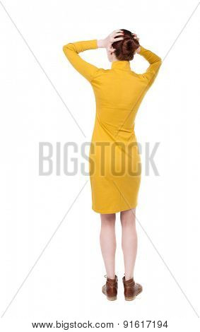 Back view of shocked woman in dress. upset young girl. Rear view people collection.  backside view of person.  Isolated over white background. Girl in mustard simple pain her head in her hands.