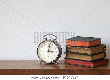 alarm clock on wooden shelf with books