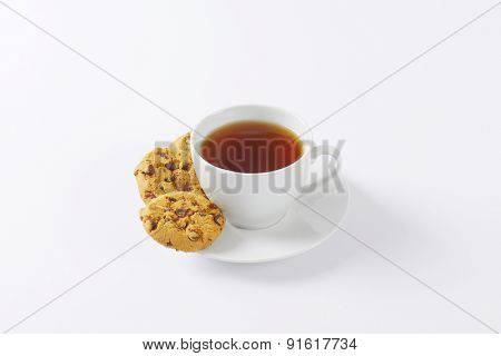 cup of tea and chocolate chip cookies on white background