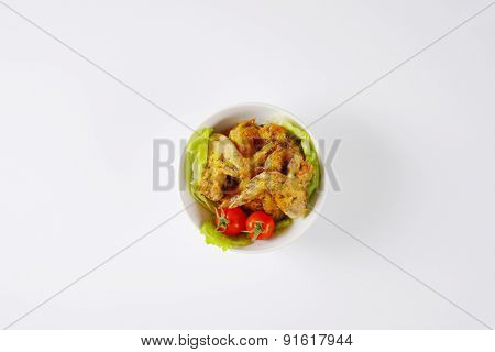 overhead view of bowl with baked chicken wings and vegetable