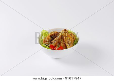 baked chicken wings, served with the salad in the bowl