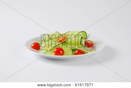 salad with thin slices of cucumber and halved cherry tomatoes, served on the round plate