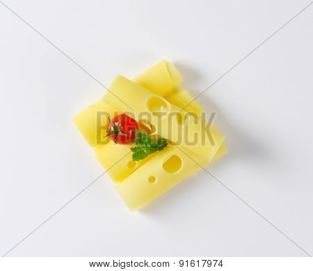 overhead view of sliced emmental cheese with cherry tomato and parsley