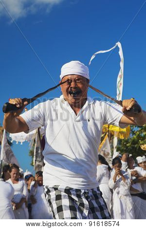 Portrait Of Balinese Man In Trance With Traditional Daggers