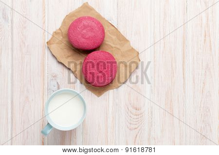 Colorful macarons and cup of milk on white wooden table with copy space