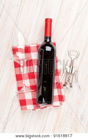 Red wine bottle, glass and corkscrew on white wooden table background. Top view