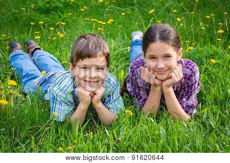 Two kids on green grass meadow