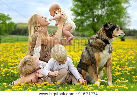 Mother And Three Children Playing In Flower Meadow