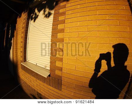 The Shadow Of A Man On The Illuminated Wall Of A House