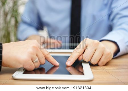 Businesswoman And Businessman Using Digital Tablet To Analyze Company Data