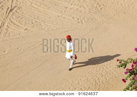 Rajasthani Man With Bright Red Turban And Bushy Mustache Walks Over The Sandy Area In The Desert Hot
