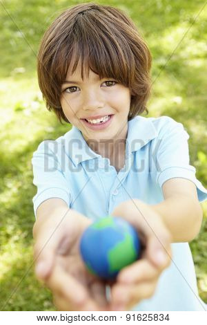 Young Boy Playing Holding Model Of Globe In Park