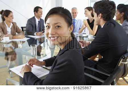 Asian Businesswoman Sitting Around Boardroom Table With Colleagues