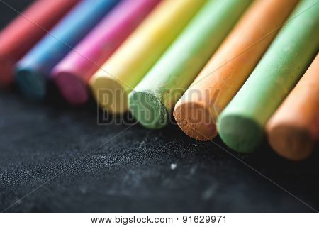 colorful pieces of chalk on blackboard