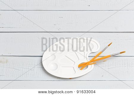 Brushes And Palette On White Wooden Planks