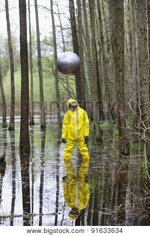 professional in protective uniform, mask, gloves with silver sphere drone above his head   in contaminated  floods area