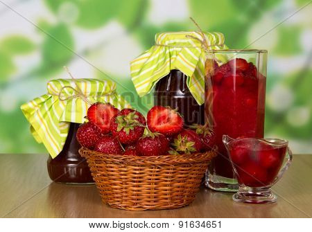 Jars of jam, strawberry in basket and glass with berries