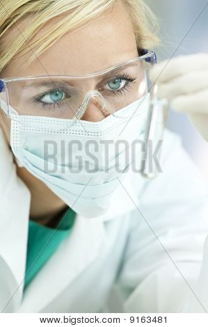 Female Scientist Doctor With Clear Solution Test Tube In Laboratory