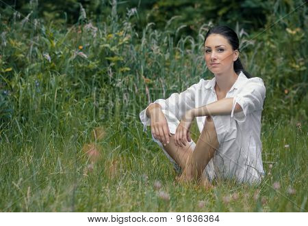 Young Woman Relaxing On Meadow, Outdoor. Adorable Vitality Girl Sitting On Grass, Daylight