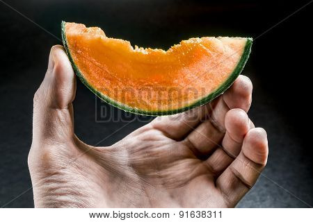 Piece Of Juicy Melon Held In Man's Hand On A Dark Background