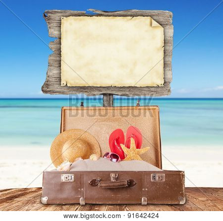 Travel concept with old suitcase on wooden planks full of beach accessories. Placed on mole with sandy beach on background and blank wooden board for text