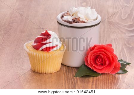 Strawberry cupcake with a cup of hot chocolate and a bright red rose on dark wooden tabletop - anniversary or Valentine's treat to a loved one