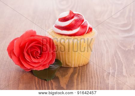 Strawberry cupcake with a beautiful red rose on wooden table, a simple treat to a loved one
