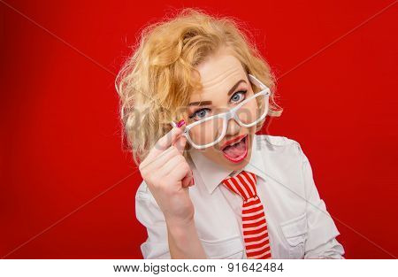 Woman Looking You Above Eyeglasses, Isolated On Red