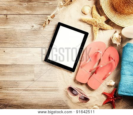 Top view of summer accessories and blank tablet on wooden planks