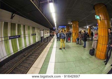 People Wait At The Metro Station For The Arriving Train