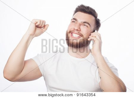 life style, tehnology  and people concept:  cheerful man on the phone with fist raised receiving good news.