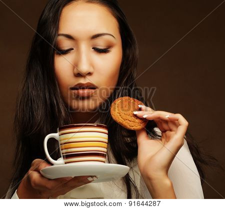 young asian woman with coffee and cookies.
