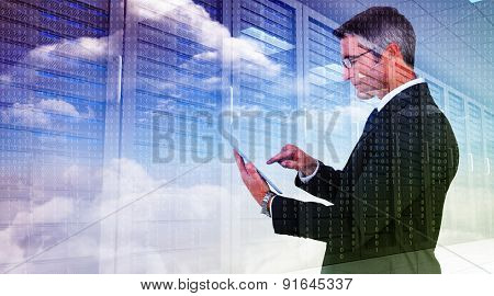 Mid section of a businessman touching tablet against server hallway