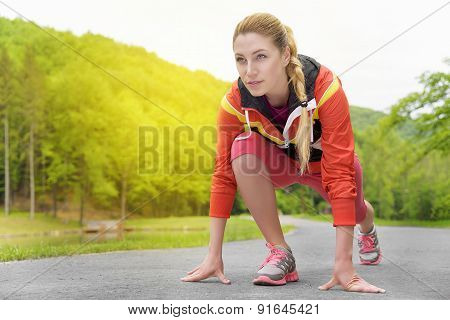 Attractive Blonde Woman Running On Track Outdoors.