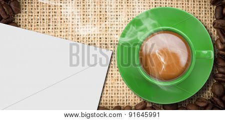Green cup of coffee against white card