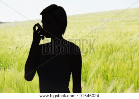 Blonde woman taking her inhaler against green meadow