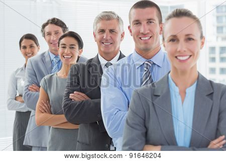 Smiling business team standing in a line in the office