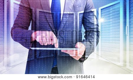 Businessman using his tablet pc against server room