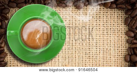 Green cup of coffee against frame of coffee beans