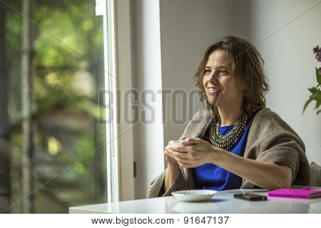 Woman sits in front of the window with a Cup of tea.