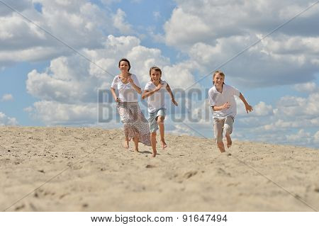 Mother with her sons running on a sand
