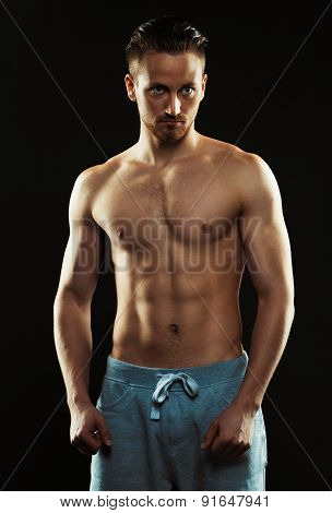 Portrait Of A Shirtless Confident Young Athletic Man Standing Against Black