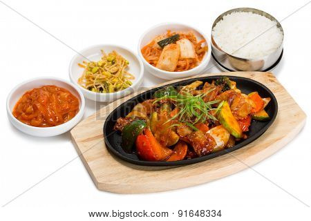 Roasted meat with vegetables in a skillet with rice and spicy salad. From a series of Food Korean cuisine.
