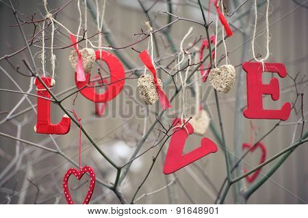 Word Love And Heart-shaped Ornaments Hanging On A Tree